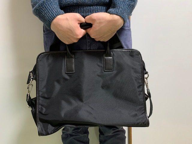 ビジネスバッグを両手で前に抱える男性