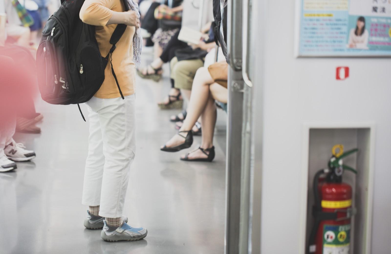 電車内で立つ男性