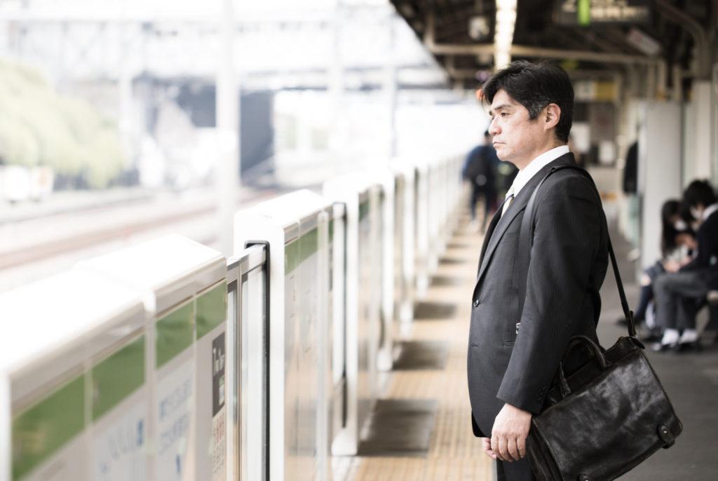 ホームで電車を待つ男性