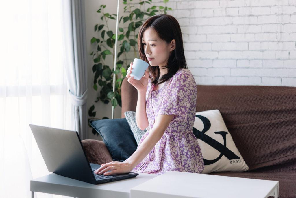 コーヒーを飲みながらリモートワークする女性