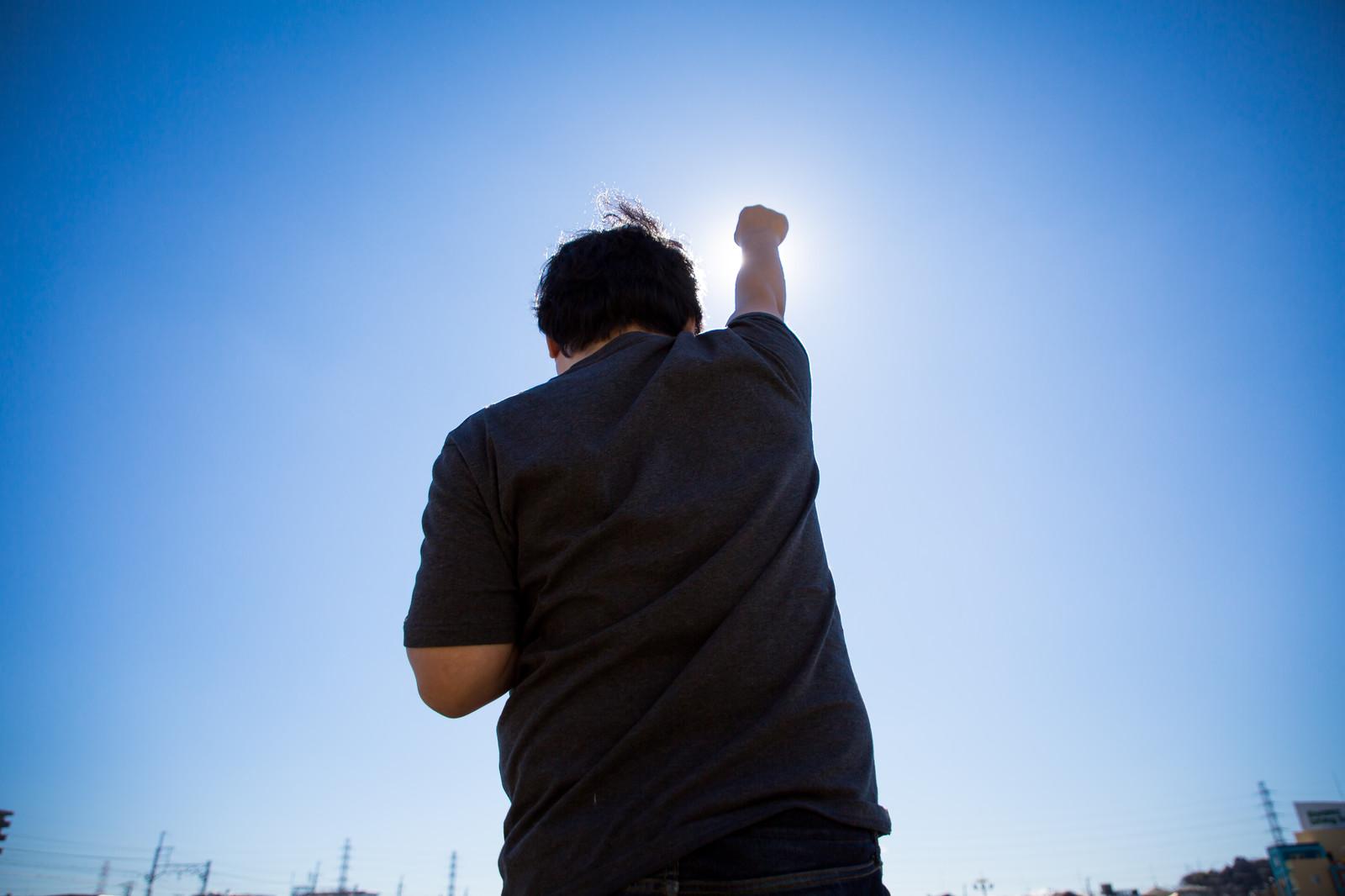 太陽に向かって拳をあげる男性の後ろ姿