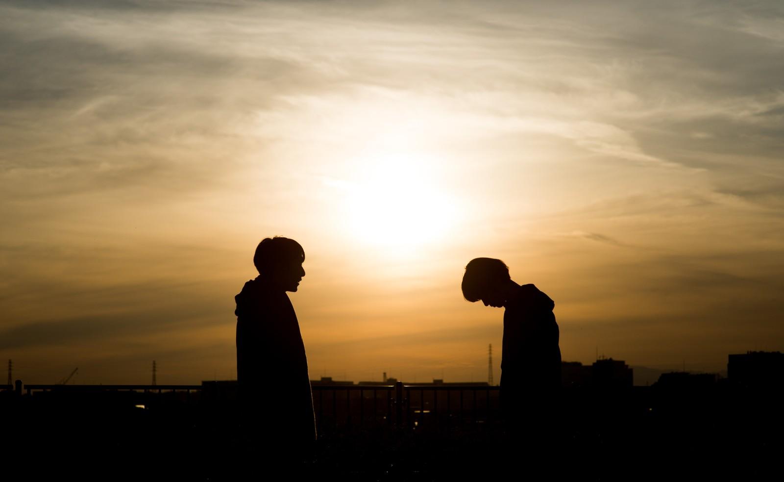 夕日を背に告白する男女