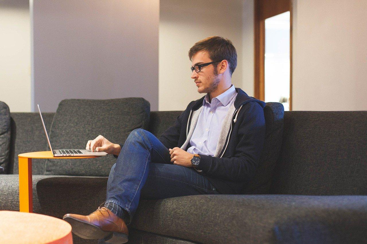 ソファに座ってパソコンをする男性