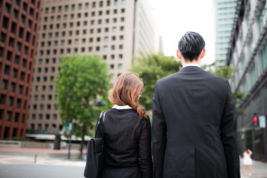 スーツ姿で信号待ちする男女
