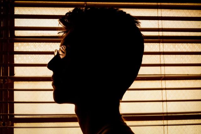 カーテンの横にたたずむ男性