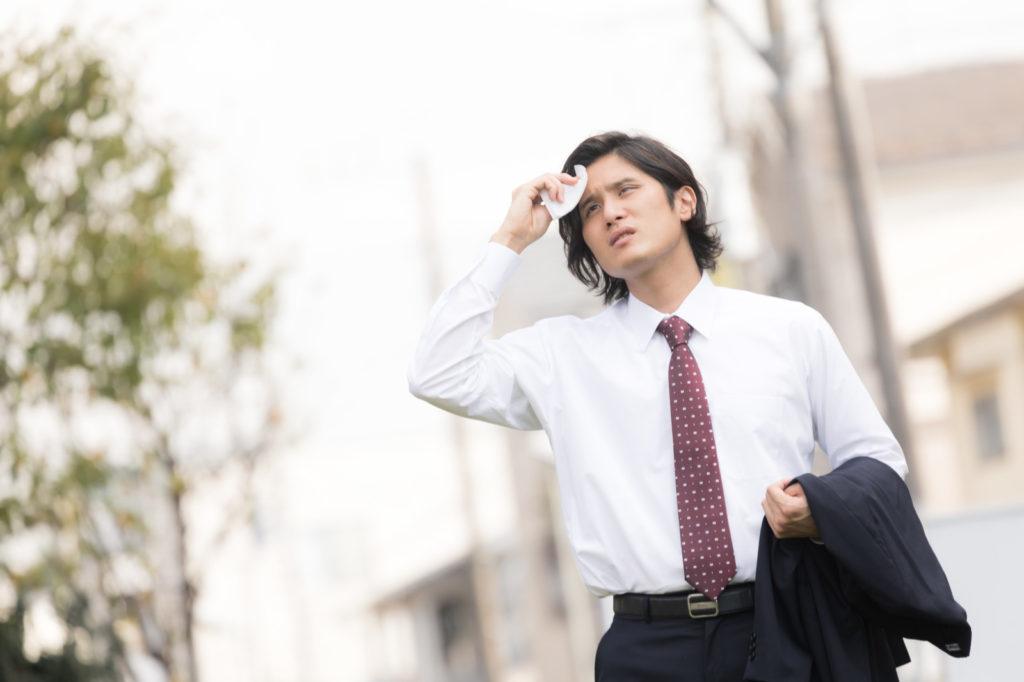 外回りの営業で汗をぬぐう男性