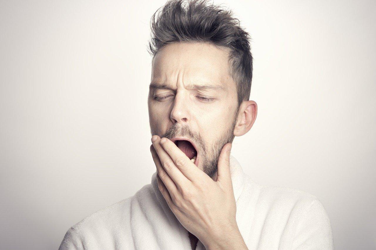 退屈そうにあくびをする男性