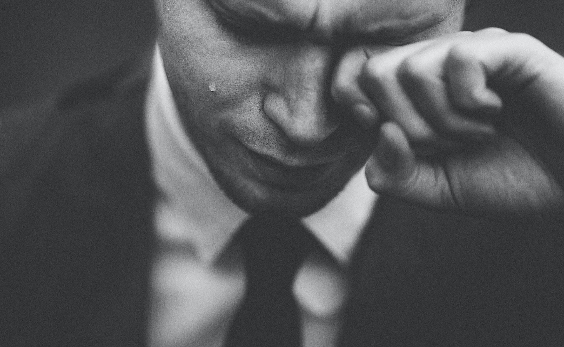 涙を流すスーツ姿の男性