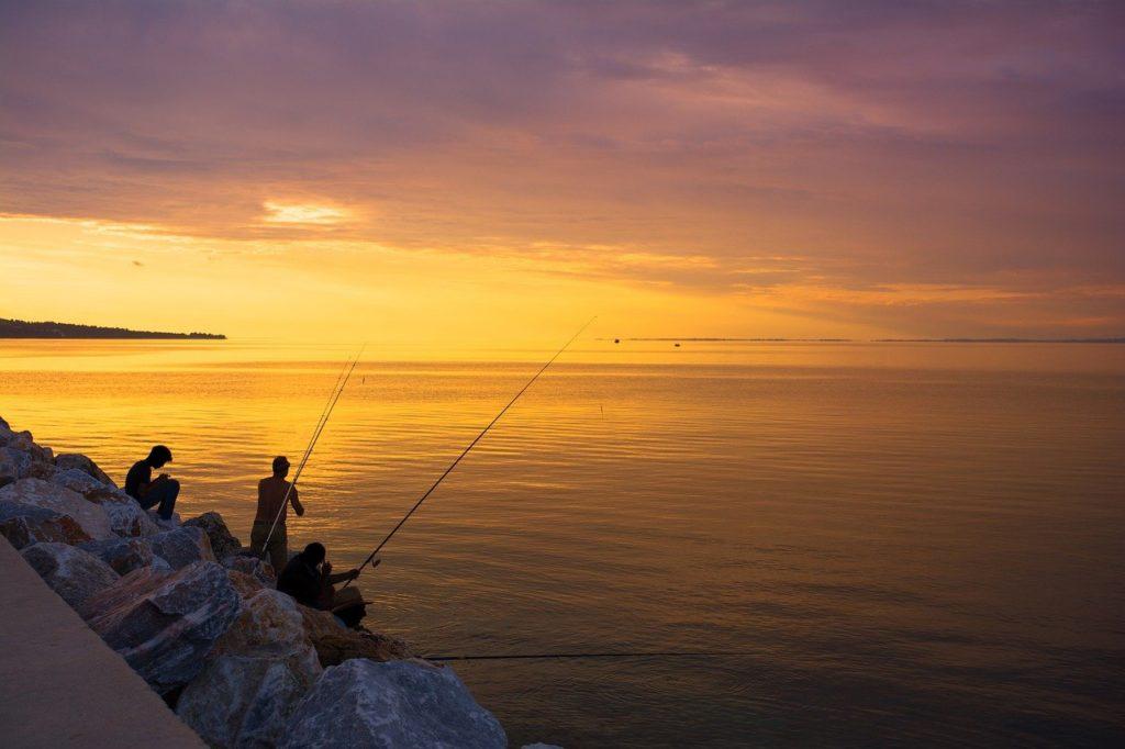 夕暮れに海辺で釣りをする人たち