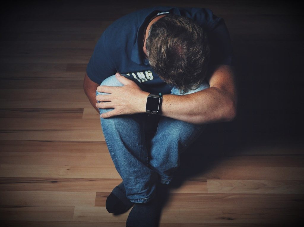 疲れて膝を抱える男性