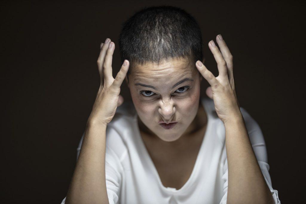 怒りを抑えきれずあらわにする女性