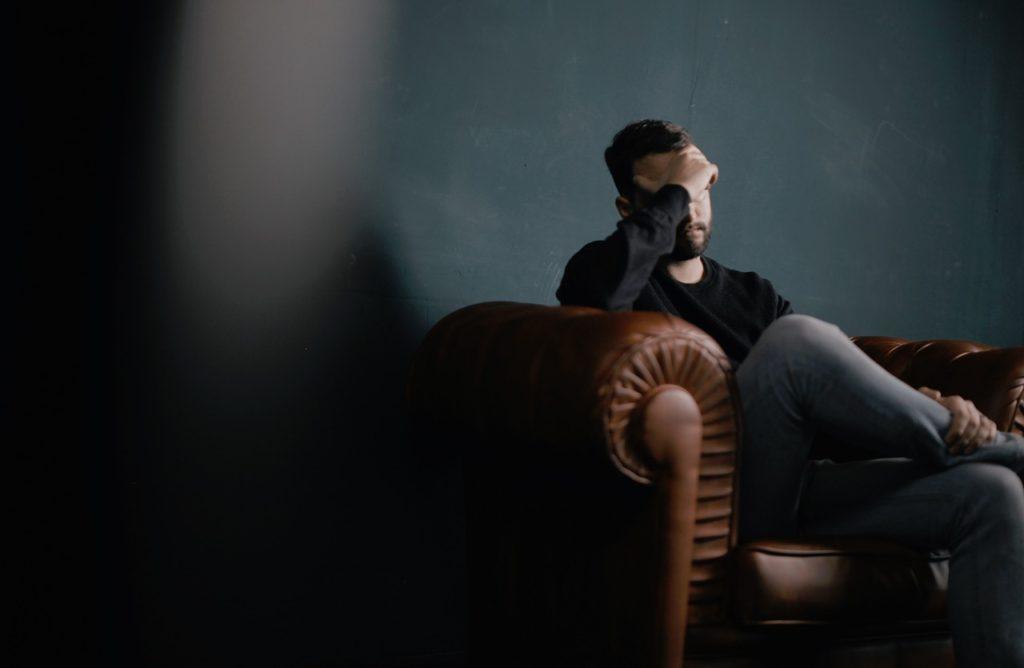ソファーで頭を抱える男性