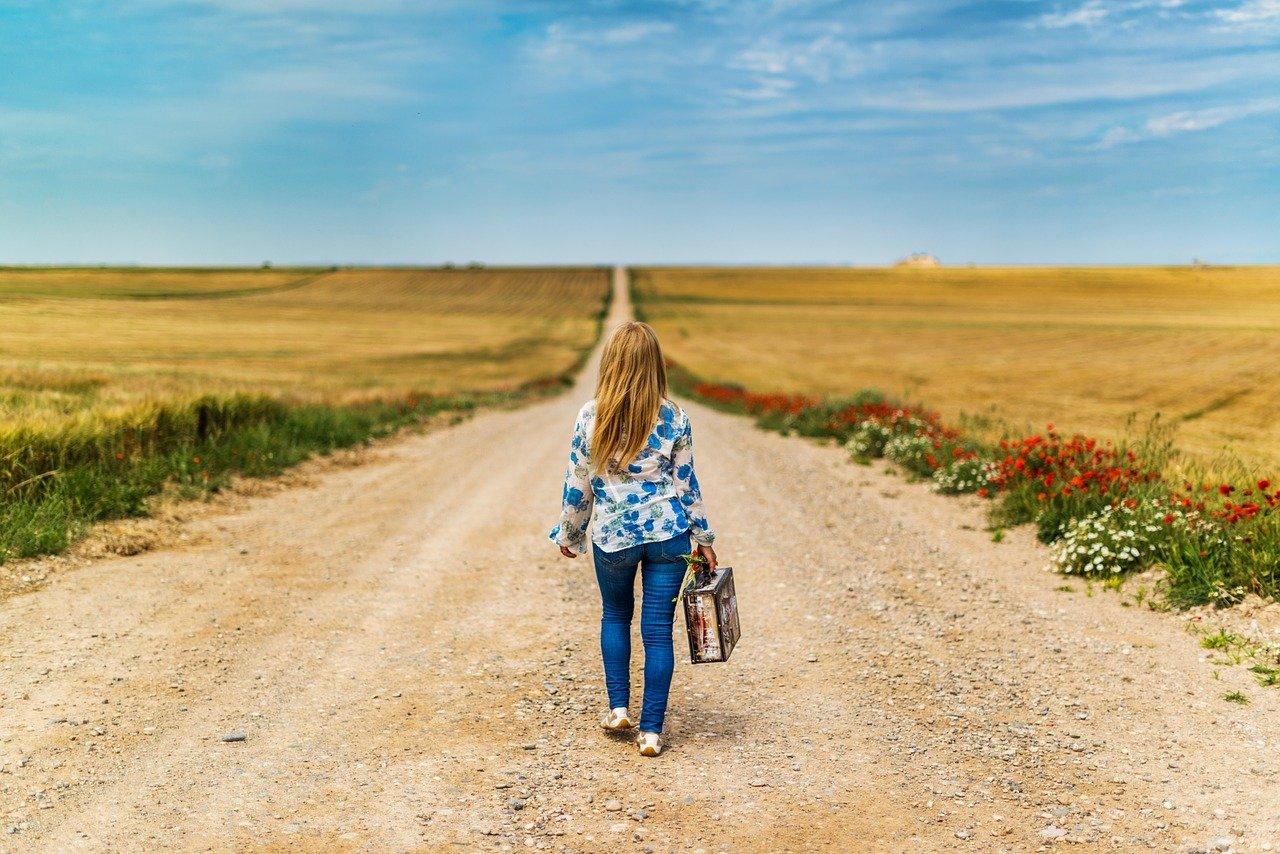 バッグひとつで広い道を歩く女性
