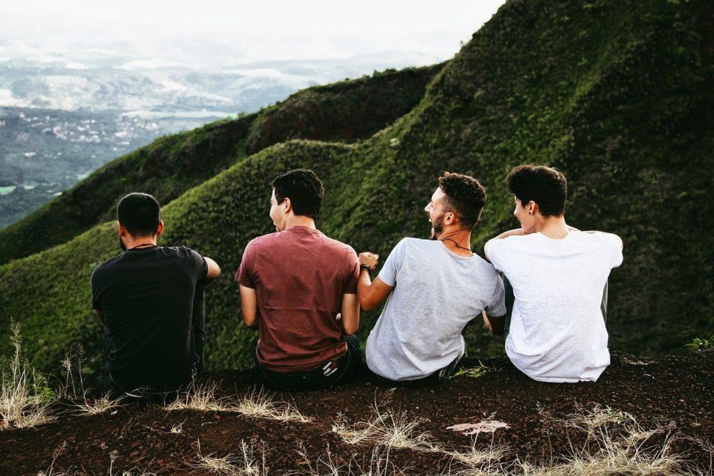 仲良さげに並んで座る4人の若者