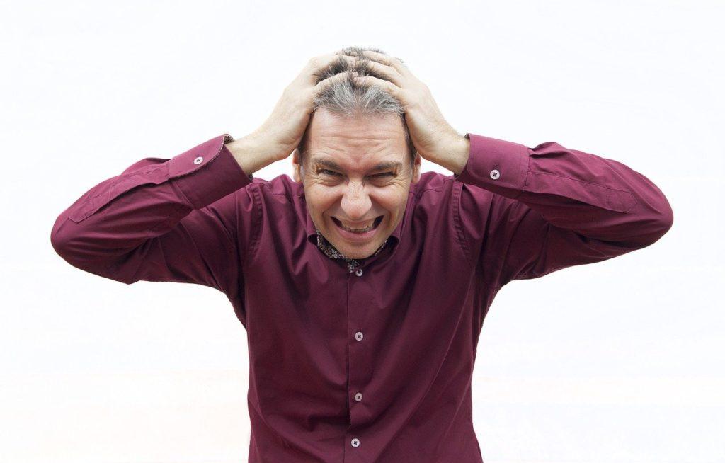 頭を抱える中年男性