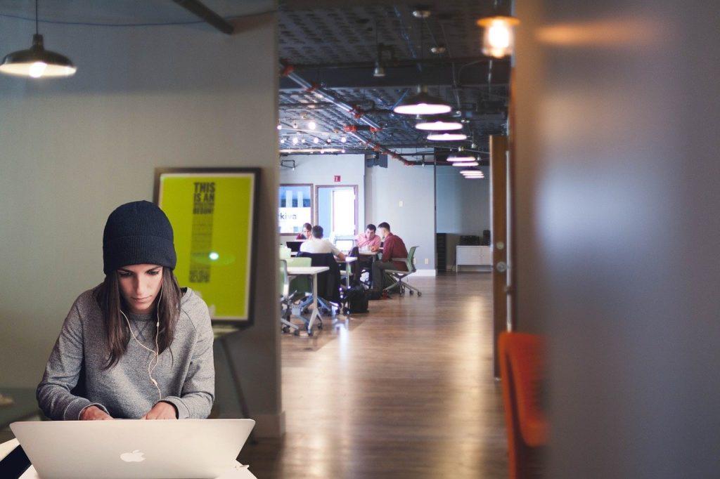 イヤホンをしながらMacbookを操作する女性