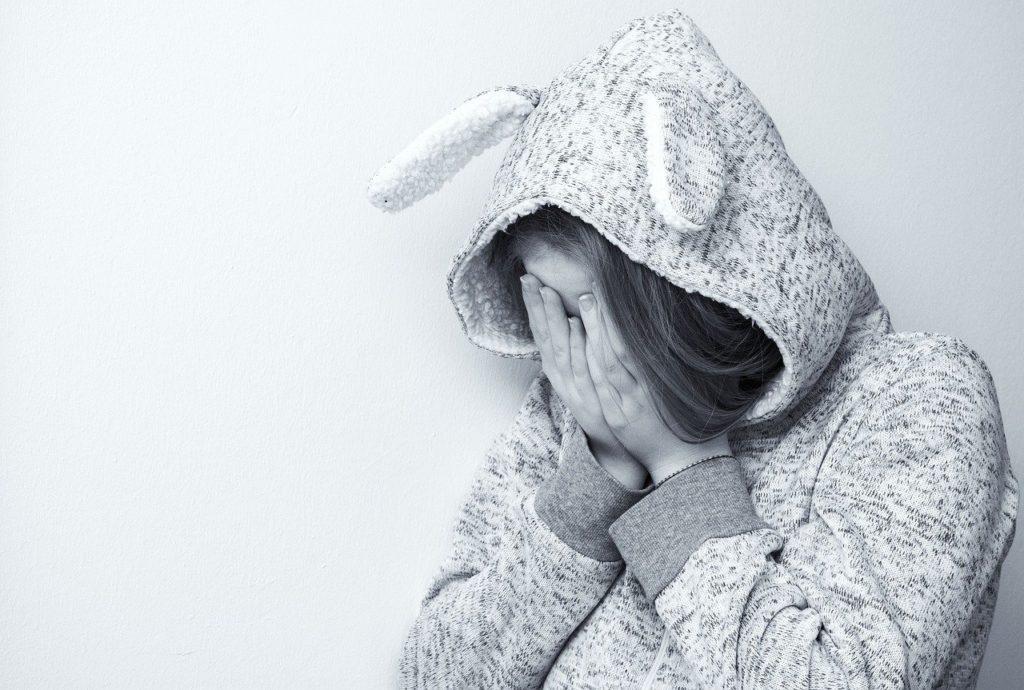 フードをかぶって目と耳を覆う女性