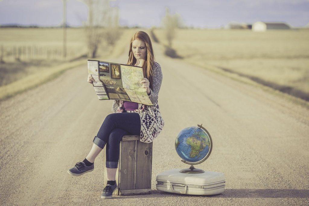 道路の真ん中で地図を広げる女性